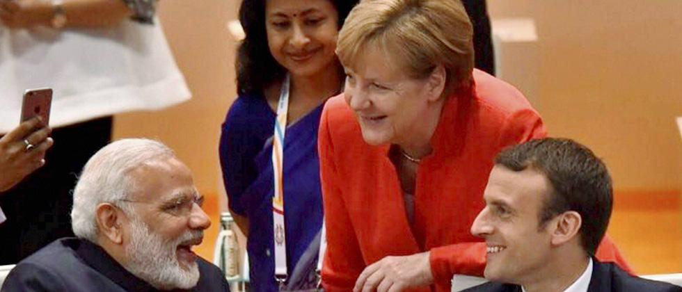 Prime Minister Narendra Modi interacts with German Chancellor Angela Merkel and French President Emmanuel Macron at the G-20 Summit in Hamburg, Germany on Friday.