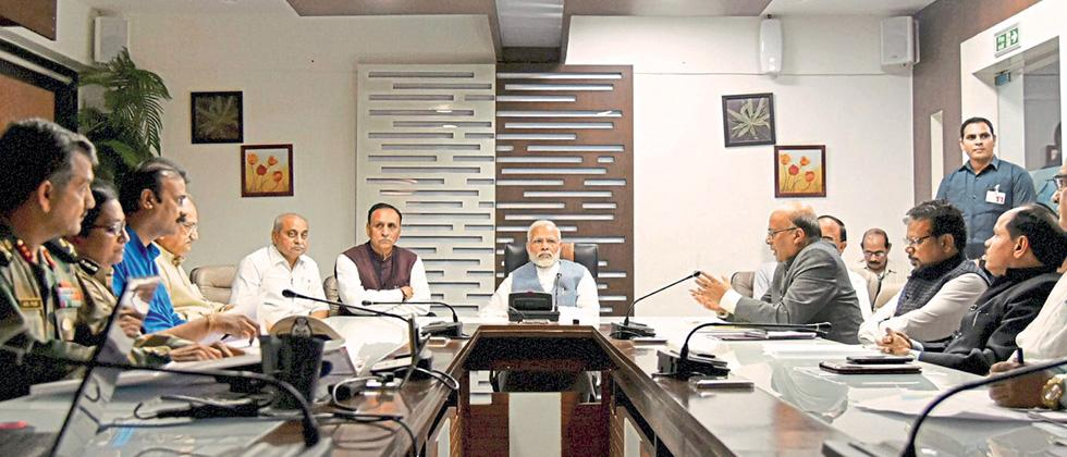 Prime Minister Narendra Modi during a meeting with officials on the situation arising out of incessant rains and floods in different parts of Gujarat State, at Ahmedabad on Tuesday.