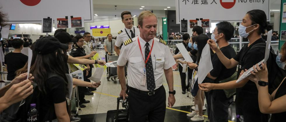Protesters greet the crew from one of the last few arriving flights at Hong Kong's international airport following a protest against the police brutality and the controversial extradition bill on Monday