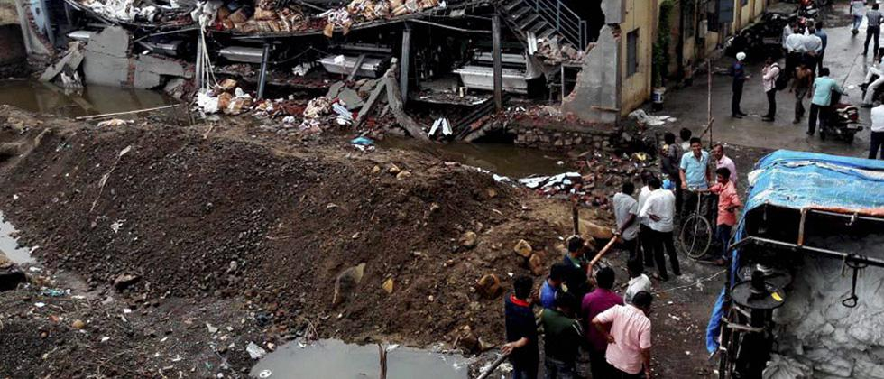 People looking at a building that collapsed after heavy rainfall in Bhiwandi, Mumbai on Saturday.
