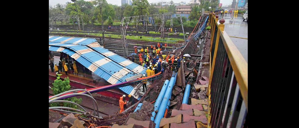 Railway and rescue workers gather around the site of the footbridge collapse in Andheri, Mumbai on Tuesday. Prashant Sawant/Sakal Times