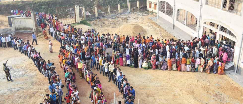 People wait in a queues to cast their votes for the Tripura Assembly Election in Agartala on Sunday. PTI Photo