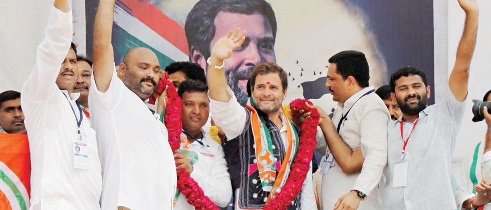 A file photo of Congress supporters garlanding Rahul Gandhi during his public meeting as part of election campaign in Dahod district of Gujarat