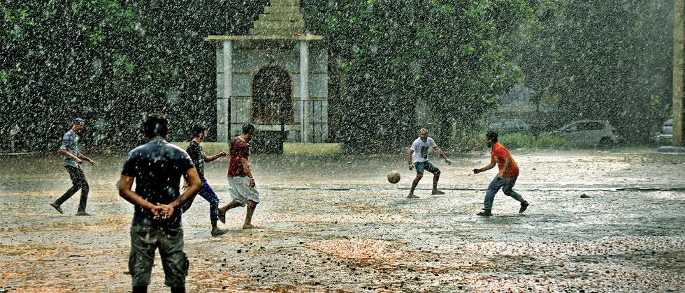 Youths playing football in the rain on Saturday. Anand Chaini/Sakal Times