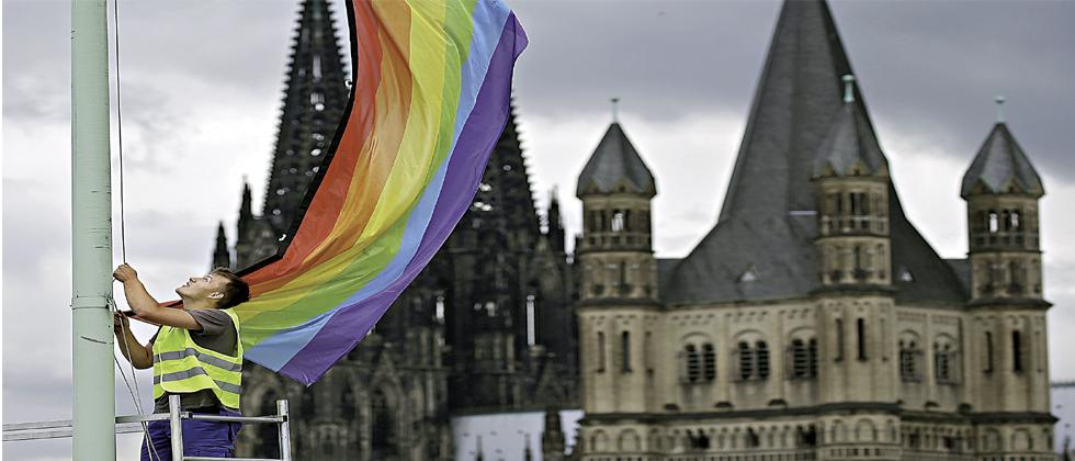 The Cologne Cathedral (L) and the church Gross St Martin (R) are seen in the background as a man hoists a rainbow flag, symbol of the gay and lesbian movement, in Cologne, western Germany recently. The German parliament has legalised same-sex marriage.