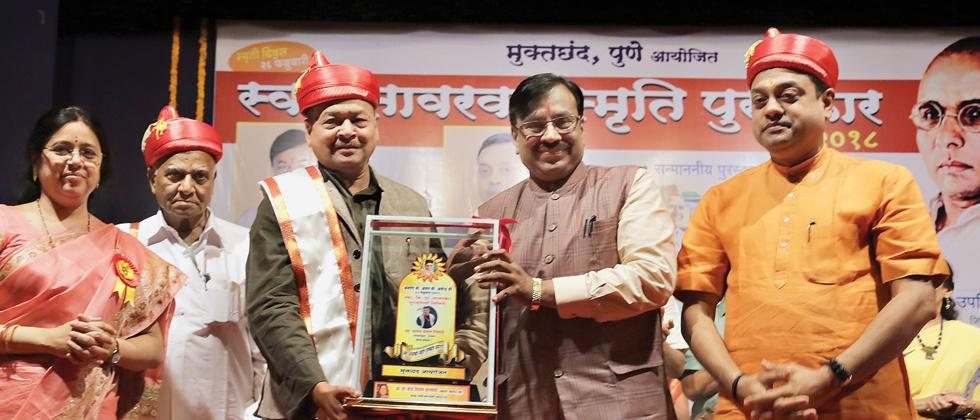 (L-R) MLA Medha Kulkarni looks on as awardees Gulam Dastagir Birajdar, Vasant Limaye receive the Savarkar Award award from Sudhir Mungantiwar and Sambit Patra at the Yashwantrao Chavan Auditorium in Kothrud on Sunday.