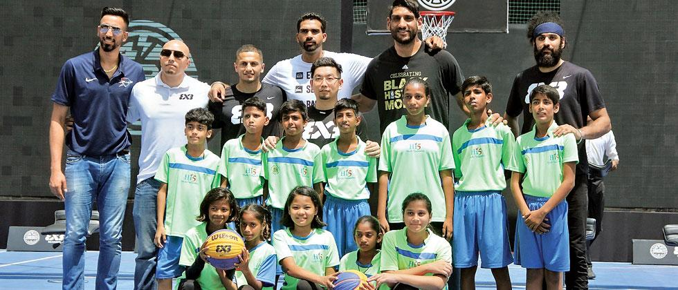 Amjyot Singh (left), Satnam Singh (2nd right) and Palpreet Singh (3rd right) pose with the children