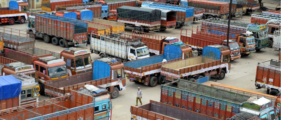 An Indian man walks past truck parked at a terminal during a nation wide indefinite strike called by truck owners against increasing fuel and toll prices, in Chennai on Wednesday