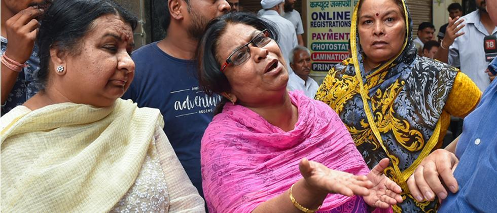 A family member of the 75-year old woman who was among the 11 members of a family found dead at a house in Burari, mourns the death of her family members outside their house, in New Delhi on Monday.