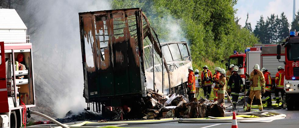Firefighters work at the scene where a tour bus burst into flames following a collision with a trailer truck on the highway A9 near Mnchberg, southern Germany, on July 3, 2017, where up to 17 people are feared dead / AFP PHOTO