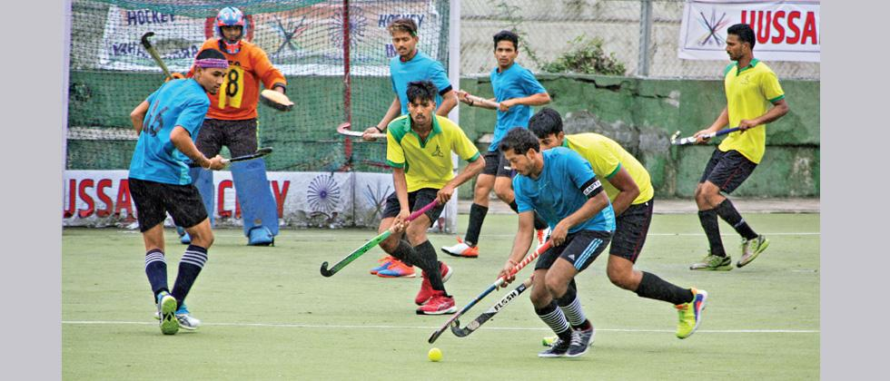 Players of Hockey United (in blue) in action against Satara XI at Major Dhyan Chand Hockey Stadium.