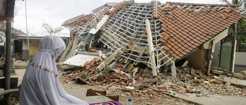 A woman performs a prayer in front of debris from Sunday's earthquake in West Lombok, Indonesia, Saturday, Aug.11, 2018. AP/PTI