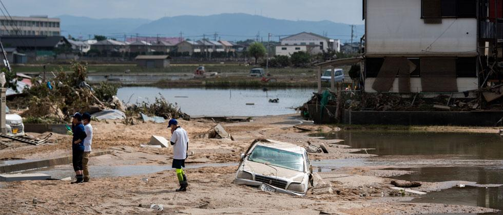 People inspect their damaged homes in a flood hit area in Mabi, Okayama prefecture on July 10, 2018. Martin Bureau/AFP