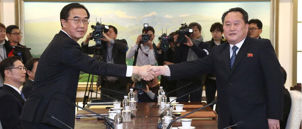 South Korean Unification Minister Cho Myoung-gyon, left, poses with head of North Korean delegation Ri Son Gwon while shaking hands during their meeting at the Panmunjom in the Demilitarized Zone in Paju, South Korea.