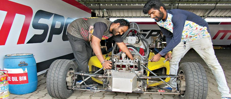 Mechanics Nagarajan (left) and Shiva Raman work on a car.