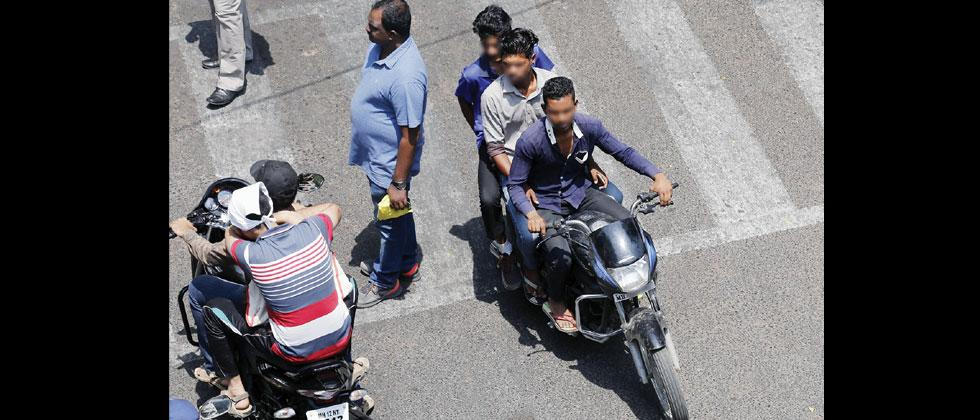 Youths riding a bike triple seat near Agriculture College in Shivajinagar