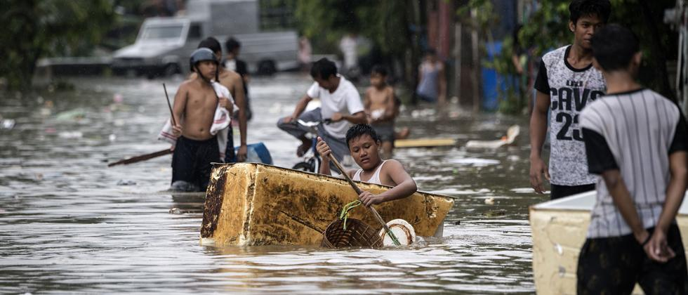 A man paddles a makeshift boat made of insulation from a refrigerator through a flooded street due to continuous rains caused by tropical depression Josie in Marikina, east of Manila on Sunday.