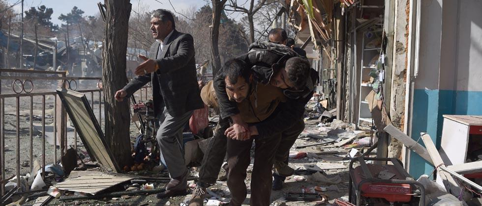 Afghan volunteers carry a body at the scene of a car bomb exploded in front of the old Ministry of Interior building in Kabul on January 27, 2018.
