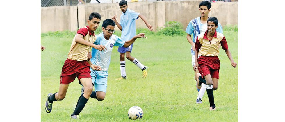 Players from Hutchings High School (blue) and St. Anthony's School chase the ball during their match in Subroto Cup at Dobarwadi Ground on Monday.