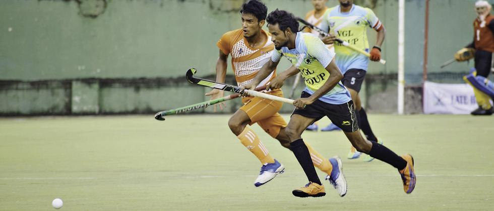 Players of Sports Authority of Gujarat (orange) in action against PCMC XI.