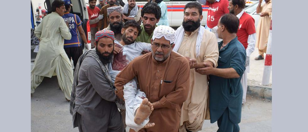 An injured Pakistani man is brought to a hospital in Quetta on Friday following a bomb blast at an election rally.