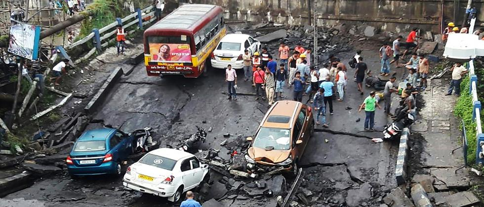 Indian commuters onlookers stand on a segment of Majerhat bridge after the bridge suddenty collapsed in Kolkata in the Indian state of West Bengal on Tuesday. - No casualties have been reported according to local media.