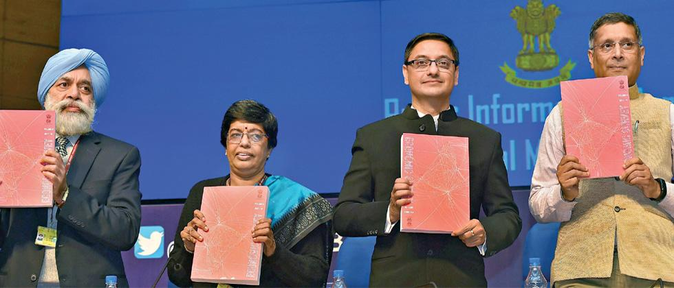 Chief Economic Adviser Arvind Subramanian (R) and finance ministry officials hold copies of the annual Economic Survey 2017-18 that was tabled in Parliament in New Delhi on Monday.