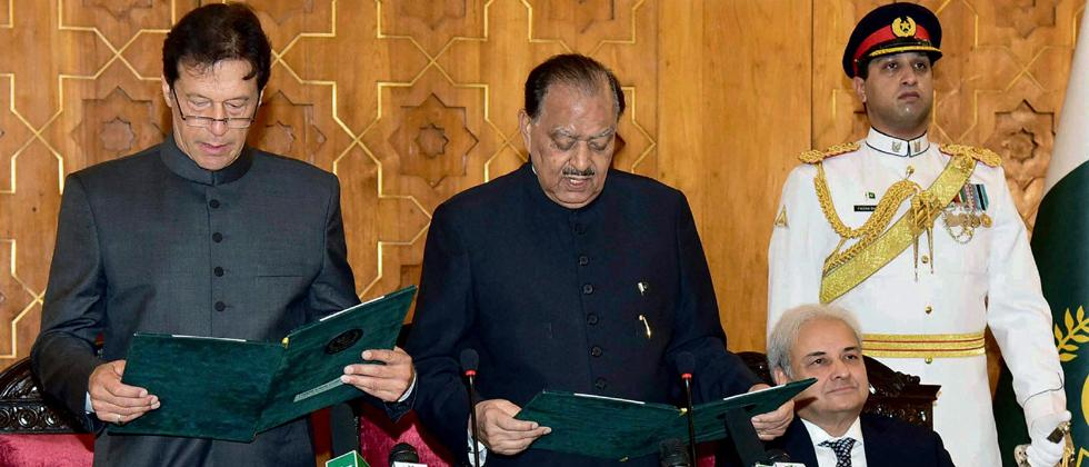 Photo released by Pakistan's Press Information Department, Pakistani President Mamnoon Hussain (C) administers oath to newly-elected Prime Minister Imran Khan (L) at Presidential Palace in Islamabad Pakistan on Saturday.