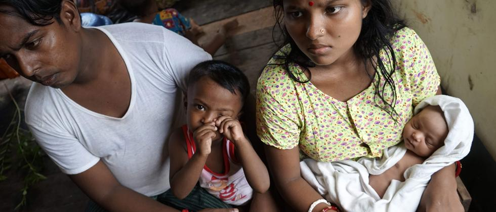 20-year-old Hindu girl, Chaw Shaw Chaw Thee (R) sits with her newborn baby, her husband and their young son at a shelter for refugees in Sittwe, on September 22, 2017. Chaw shaw Chaw Thee fears that twenty-three members of her family are dead, after Myanm