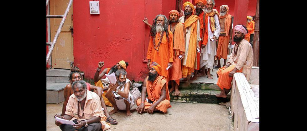 Sadhus wait in a queue for the registration for Amarnath Yatra, which commences tomorrow, in Jammu on Tuesday, June 26, 2018. PTI Photo