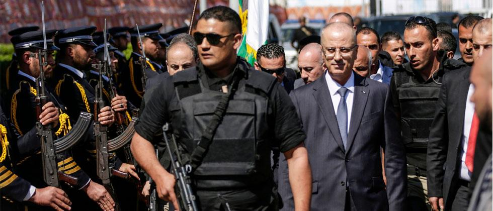 Palestinian Prime Minister Rami Hamdallah (2nd-R), escorted by his bodyguards, is greeted by police forces of the Islamist Hamas movement (L) upon his arrival in Gaza City on March 13, 2018. Photo/Mahmud Hams/AFP