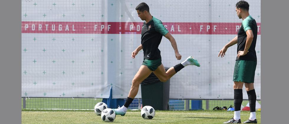 Portugal's forward Cristiano Ronaldo (L) kicks the ball as defender Pepe looks on during a training session at the team's base in Kratovo, on Saturday on the eve of the team's round of sixteen football match.