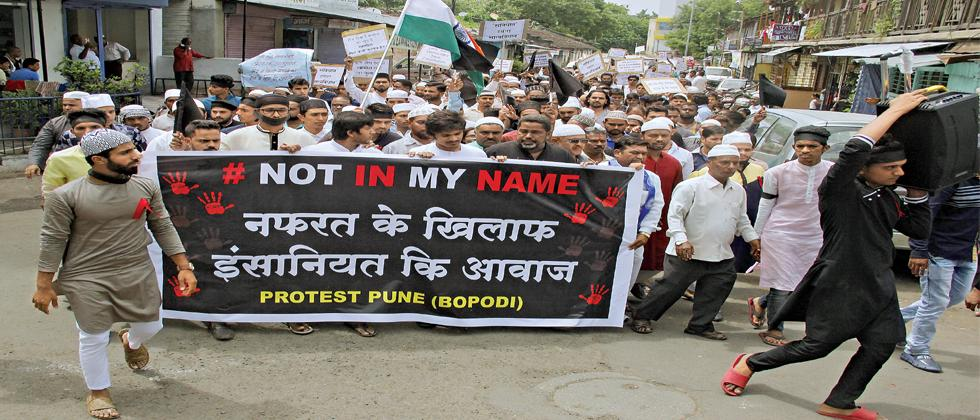 Protesters hold a banner at the 'Not In My Name' rally in Bopodi on Friday.