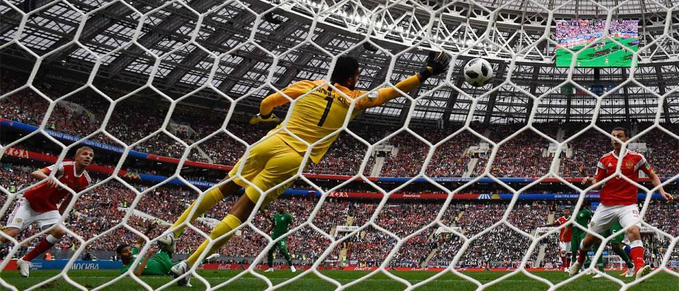 Russia's midfielder Yuri Gazinskiy (L) scoring the opening goal past Saudi Arabia's goalkeeper Abdullah Al-Mayouf. Alexander Nemenov/AFP