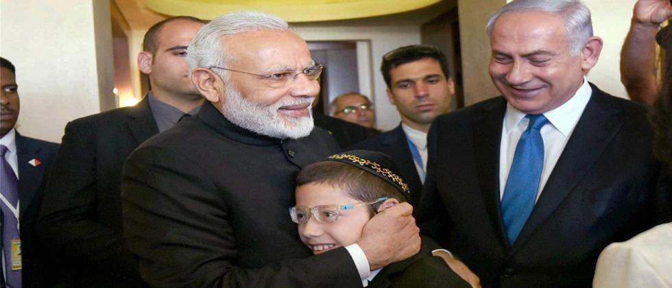 Prime Minister Narendra Modi hugs 11-year-old Moshe Holtzberg, one of the survivors of the 26/11 Mumbai terror attacks, in Jerusalem, Israel on Wednesday. Prime Minister of Israel, Benjamin Netanyahu is also seen. PTI Photo