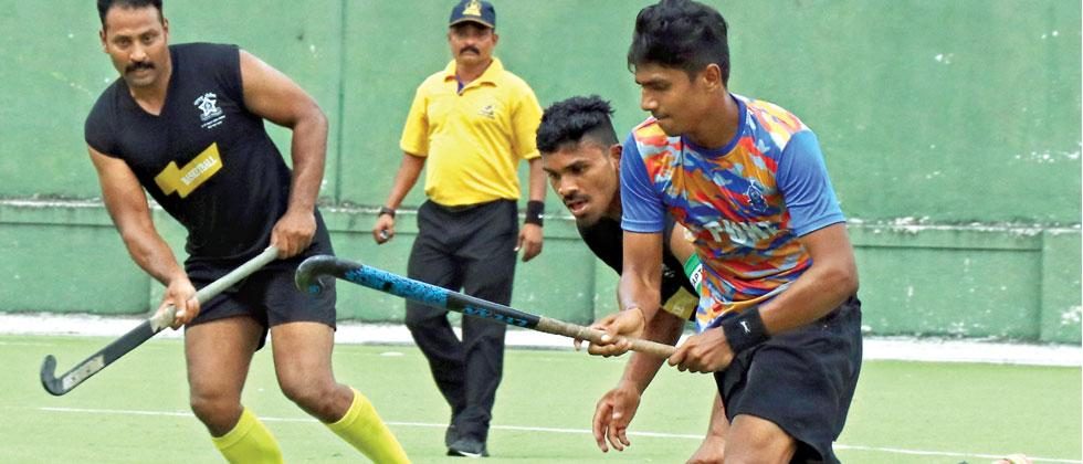 A player from Central Railway (in bule) hits the ball during their match against Railway Police in a 9-A-Side Hockey Tournament at Major Dhyanchand Hockey Stadium on Saturday