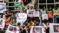 Palestinian youths and children demonstrate with Palestinian flags in Gaza City on July 15, 2018 outside a building that was struck by an Israeli air raid the day before. Mahmud Hams/AFP