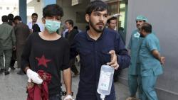 An injured youth is escorted to a hospital following a deadly attack outside the Rural Rehabilitation and Development Ministry in Kabul, Afghanistan on Sunday.