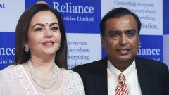 India's richest man and oil-to-telecom conglomerate Reliance Industries chairman Mukesh Ambani (R) along with his wife Nita Ambani (L) pose as they arrive for the company's 42nd AGM in Mumbai on Monday.