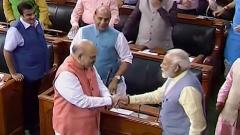 Prime Minister Narendra Modi shakes hands with Union Home Minister Amit Shah after Parliament approved the abrogation of special status given to J&K under Article 370, in the Lok Sabha, in New Delhi, on Tuesday.