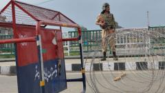 A security personnel stands guard on a street during a lockdown in Srinagar on Sunday.