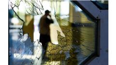 A man is seen through a broken window of a wedding hall after a deadly bomb blast in Kabul.